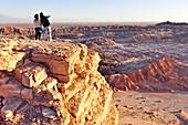 Young couple on a rock enjoys view at sunset, Valle de la Luna, Valley of the moon, Atacama desert, National Reserve, Reserva Nacional Los Flamencos, Region de Antofagasta, Andes, Chile, South America