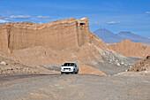Jeep on track between mountains and rock formations, Valle de la Luna, Valley of the moon, Atacama desert, National Reserve, Reserva Nacional Los Flamencos, Region de Antofagasta, Andes, Chile, South America