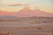 'Junges Paar fährt mit Farrad durch Wüste, im Hintergrund Vulkan Licancabur im Sonneuntergang, Valle de la Luna, Tal des Mondes, Atacama Wüste, Reserva Nacional Los Flamencos, Region de Antofagasta, Anden, Chile, Südamerika, Amerika;'