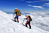 Mountain climbers with ice axe on snow field over the clouds, volcano Villarrica, Strato volcano, sunset, National Park Villarrica, Pucon, Región de la Auracania, Region Los Rios,  Patagonia, Andes, Chile, South America