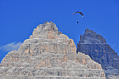 Paraglider flies through Three Peaks, Val Pusteria Valley, Sesto, Dolomites, South Tyrol, Veneto, Alto Adige, Three Peaks, Tre Cime di Lavaredo, Drei Zinnen, Nature Park, UNESCO world heritage side, Italy, European Alps, Europe
