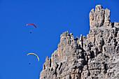 Paraglider flying through rocks of Three Peaks, Val Pusteria Valley, Sesto, Dolomites, South Tyrol, Veneto, Alto Adige, Three Peaks, Tre Cime di Lavaredo, Drei Zinnen, Nature Park, UNESCO world heritage side, Italy, European Alps, Europe