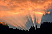Sunrays before sunrise behind mountain range Rosengarten, Catinaccio, St. Zyprian, Tiers, Tiers Valley, Nature Park Schlern Rosengarten, Dolomites, South Tyrol, Alto Adige, UNESCO world heritage side, Italy, European Alps, Europe