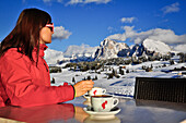 Young woman drinking coffee in winter at snow covered Seiser Alm with Langkofel und Plattkofel, Seiser Alm, Alpe di Siusi, Sciliar, Nature Park Schlern-Rosengarten, Dolomites, South Tyrol, Alto Adige, UNESCO world heritage side, Italy, European Alps, Euro