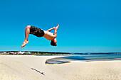 Man jumping from the dunes, Lagoa de Santo Andre, Santiago do Cacem, Costa Vicentina, Alentejo, Portugal