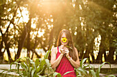 Woman smiles behind a sunflower in her garden during golden hour