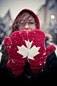 A woman places her mittens side by sde to create a  Canadian Maple Leaf.