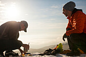 Two climbers converse while  cooking breakfast in the mountains of British Columbia, Canada.