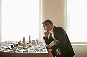 Caucasian architect examining urban model in office