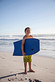 Caucasian by carrying boogie board on beach