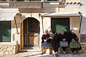 Elderly Corfiot women wearing traditional black clothes sitting relaxing in village square of Krini, Corfu, Greek Islands, Greece, Europe