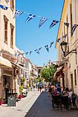 Flags hang over a narrow street, Chania, Crete, Greece