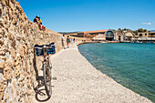 Bicycle and pedestrians on the wall along the Venetian harbour, Chania, Crete, Greece