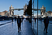 Pedestrians on a walkway with London's tower bridge in the background, London, England