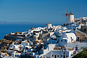 An old windmill above traditional painted houses, Oia, Santorini, Cyclades, Greek Islands, Greece