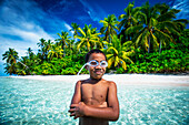 A Tuvalu boy wearing goggles on an island that forms part of a marine park just off the Tuvalu mainland, Tuvalu