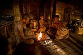 Goroka mudmen gathered around a fireplace, Goroka, Eastern Highlands, Papua New Guinea