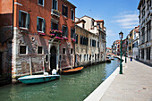A small canal with boats and lamp posts lining the walkway, Venice, Italy