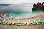 Beach chairs along the water's edge and a view of the horizon, Monterosso Al Mare, Liguria, Italy