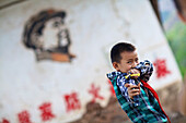 Boy with slingshot in front of Chairman Mao mural, Yunnan, China