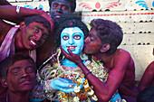 Men painted red during Holi festival, Kolkata, West Bengal, India