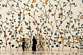 Mother and son in front of decorated wall in the Sheikh Zayed Grand Mosque, Abu Dhabi, United Arab Emirates
