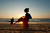 Silhouette of a woman selling Indian cloth on the beach at dusk, Candolim, Goa, India