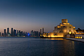 Museum of Islamic Art at dusk with modern city skyline behind, Doha, Qatar