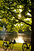 Couple relaxing beside lake in the Vondelpark in the evening, Amsterdam, Holland