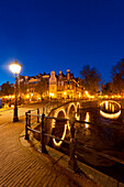 Bridges over canals at dusk with streak of lights from boat, Amsterdam, Holland
