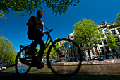 Silhouette of man cycling past canal, Amsterdam, Holland