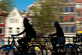 Silhouette of cyclists going past canal and gabled houses, Amsterdam, Holland