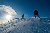 Walkers climbing the snowy slopes of Sgorr Dhearg near Glen Coe, Highlands, Scotland