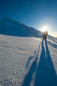 Walkers descending the snowy slopes of Sgorr Dhearg in winter near Glen Coe, Highlands, Scotland