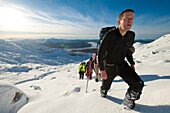 Walkers going through heavy snow up Beinn Respiol, Ardnamurchan peninsula, Highlands, Scotland