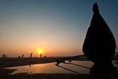 Bow of old boat on beach at dusk, Goa, India