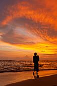 Mother and baby watching sunset on beach, near Unawatuna, Thalpe, Sri Lanka