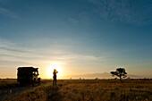 Silhouette of woman looking through binoculars in front of Mt Kenya at dawn, Ol Pejeta Conservancy, Kenya