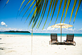 Deck chairs under parasol on white sandy beach with palm trees overlooking blue sea, Cenang beach, Pulau Langkawi, Malaysia