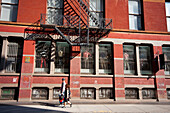 Couple Passing By An Apartments Building In Tribeca, Manhattan, New York, Usa
