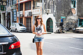A young female tourist walks on the street in Georgetown, Little India and Chinatown areas, Penang, Malaysia