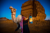 Camel and rider with Madain Saleh in the background, Madain Saleh, Saudi Arabia