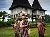 Elderly men in traditional attire standing in front of distinctive houses, Timor-Leste