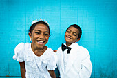 Children dressed in white formal wear against a blue wall, Hapai Island, Tonga