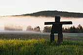 'Large rock Inuit inukshuk in grassy field with morning fog in the distance and trees with rolling hills; Alberta, Canada'