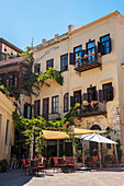 'Yellow residential building and restaurant patio; Chania, Crete, Greece'