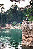 'A girl waits to jump from this cliff and swim outside the Seven kilometre caves; Kong Lor, Laos'