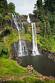 'A group of travelers gather to play in the Tad Yuang Waterfall on the Bolaven Plateau; Laos'