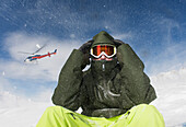 'A young man sits in winter apparel and a ski mask while a helicopter flies overhead and blows snow; Methven, New Zealand'