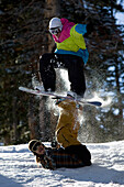 'Two snowboarders have fun doing a balance trick in the snow; Utah, United States of America'